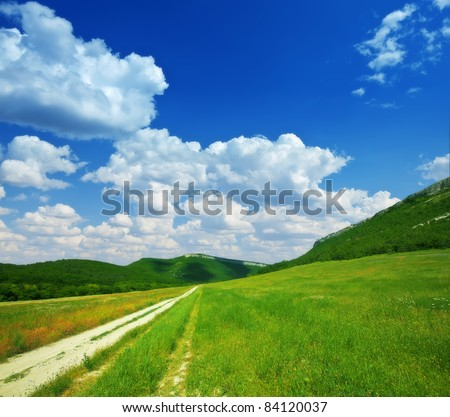 steppe road in mountains on a background cloudy sky - stock photo
