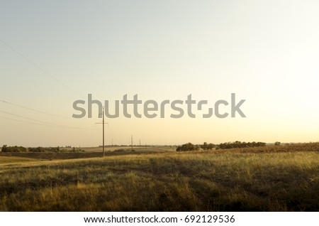 Steppe Ukrainian landscapes at the end of summer. Sultry evening,  long shadows of trees and dirt road.