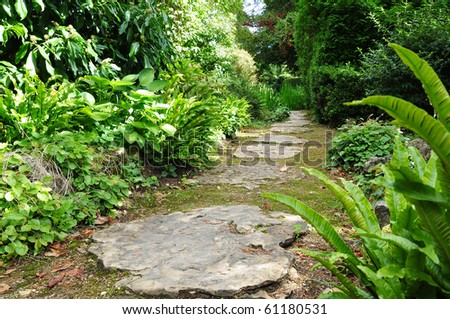 Stepping Stone Path in a Beautiful Green Garden - stock photo