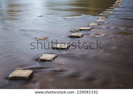 Stepping stones crossing a river. - stock photo