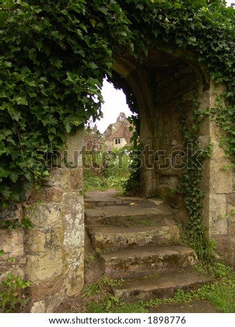 Steps going up through old garden archway - stock photo