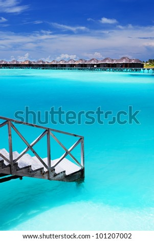 Steps into amazing blue lagoon with over-water bungalows - stock photo