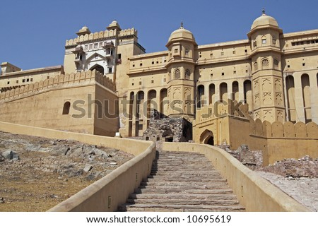 Steps leading up to the imposing front entrance (Suraj Pol) to Amber Fort. Large honey coloured Moghul style building. Jaipur, Rajasthan, India.