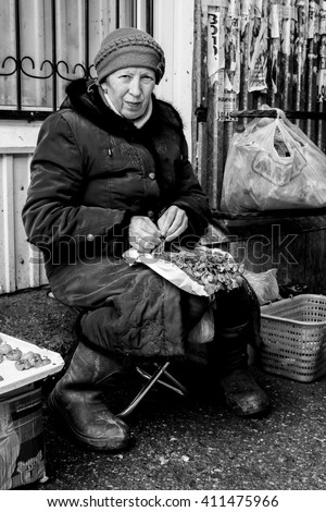 STERLITAMAK - RUSSIA 9TH APRIL 2016 - A Russian market seller sitting down and tying bundles of parsley herbs together for people to buy at a local market in Russia in April 2016.