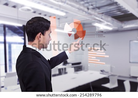 Stern asian businessman pointing against classroom - stock photo