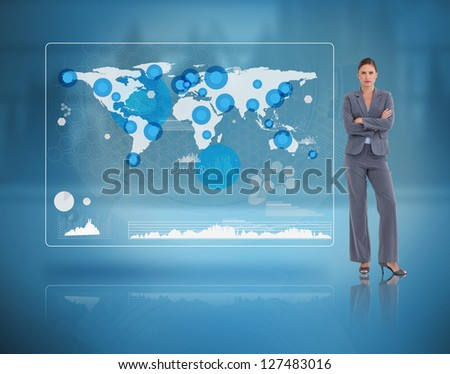 Stern businesswoman standing against a futuristic screen with the world map