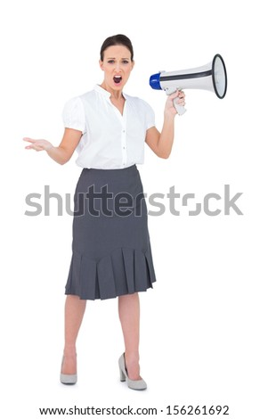 Stern businesswoman yelling in her megaphone while posing on white background