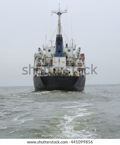 Stern of the ship in close up with working screw and rudder view back ship in the sea - stock photo