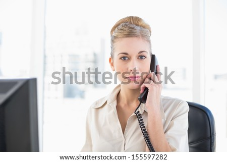 Stern young blonde businesswoman answering the telephone at office