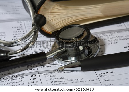 Stethoscope, a pen and a blank prescription pad - stock photo