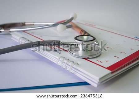 stethoscope and calendar  with Blank medical clipboard - stock photo