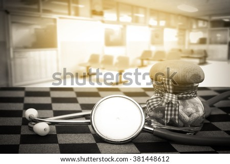 stethoscope and capsule bottle with blur chair in hospital background