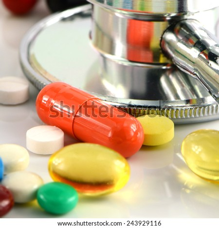 Stethoscope and Colorful of oral medications on White Background. - stock photo