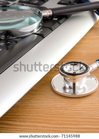 stethoscope and laptop with magnifier on wooden table - stock photo