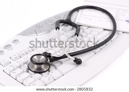 Stethoscope and medical record lying on a keyboard. Focus on the foreground. - stock photo