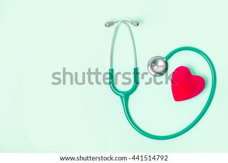 Stethoscope and red heart on green background - stock photo