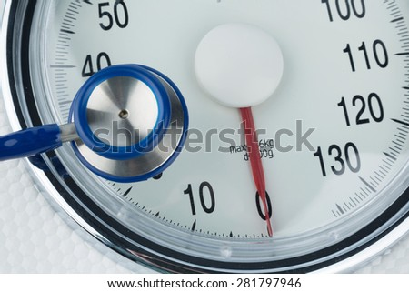 stethoscope and scale, symbol photo for weight, diet and heart disease - stock photo
