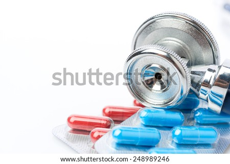 Stethoscope and some pills - isolated on a white background - stock photo