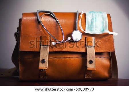 Stethoscope and surgical mask on doctor's bag. - stock photo