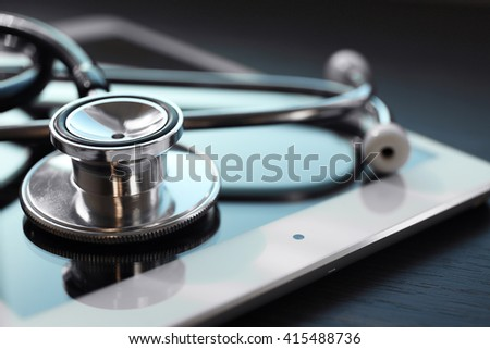 Stethoscope and tablet on dark wooden background - stock photo
