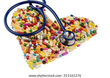 stethoscope and tablets in heart-shaped arrangement, symbolic photo for heart disease, diagnosis and medication - stock photo