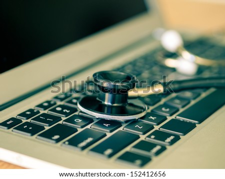 Stethoscope closeup on a laptop - close up - stock photo