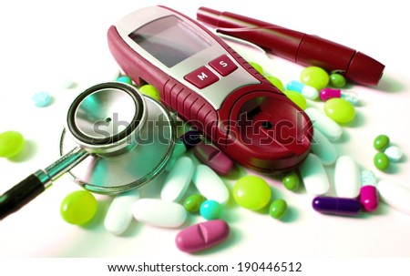 stethoscope,device for measuring blood sugar level and different kind of pills - stock photo