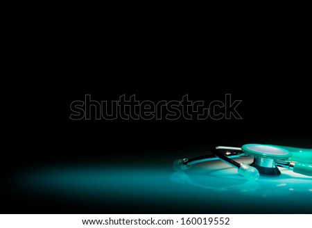 Stethoscope in a spotlight on blue reflective table and black background - stock photo