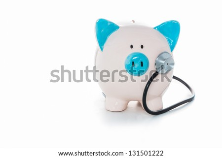 Stethoscope listening to blue and white hand painted piggy bank - stock photo