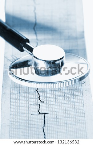 Stethoscope lying on ECG diagram - stock photo