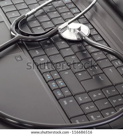 Stethoscope lying on the keyboard - stock photo