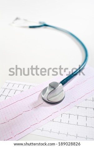 Stethoscope lying on the printout of an ECG. - stock photo