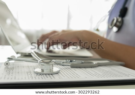 Stethoscope, medical document with the doctor using computer in room at hospital. - stock photo