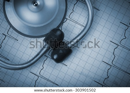 Stethoscope on a background of an electrocardiogram concept - stock photo