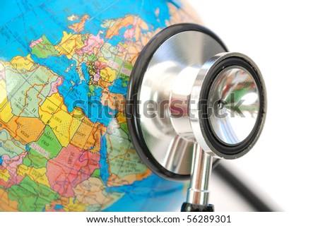 Stethoscope on a globe - stock photo