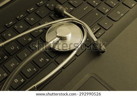 Stethoscope on black laptop keyboard - stock photo