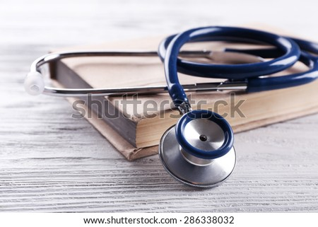 Stethoscope on book on wooden table, closeup - stock photo