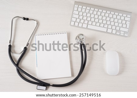 Stethoscope on doctor's desk with keyboard and pad - stock photo