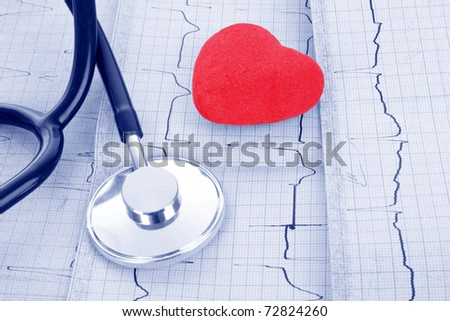 Stethoscope on ECG and red heart - stock photo
