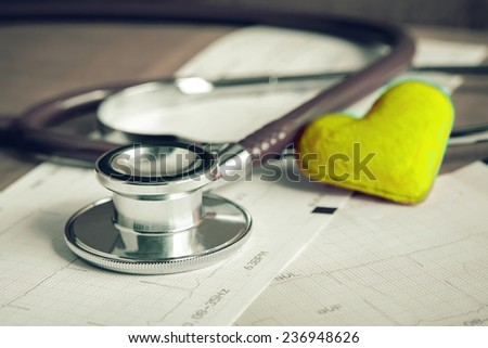 Stethoscope on electrocardiogram paper report with yellow heart  - stock photo