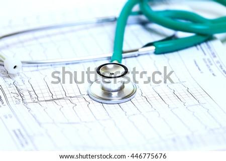 Stethoscope on heart cardiogram - stock photo