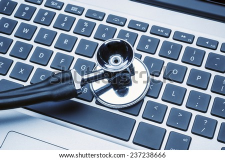 Stethoscope on laptop keyboard - stock photo