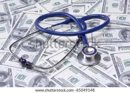 Stethoscope on money background of dollars - stock photo