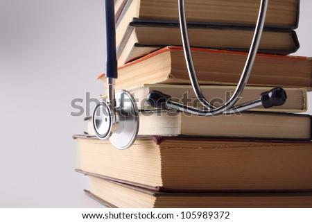 Stethoscope on pile of books isolated. Blue background - stock photo