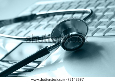 Stethoscope on silver laptop - stock photo