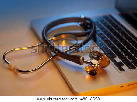 Stethoscope on silver laptop computer in blues and oranges - stock photo