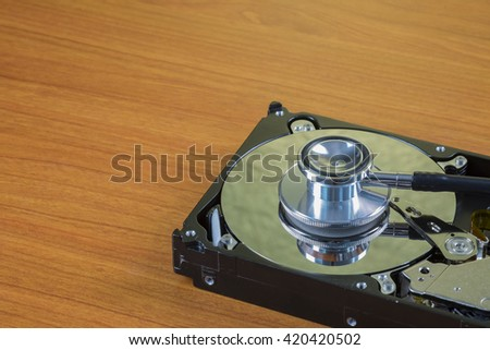 stethoscope on the hard disk drive - harddisk drive is the data storage for the digital data where is in the your computer isolate on white - stock photo