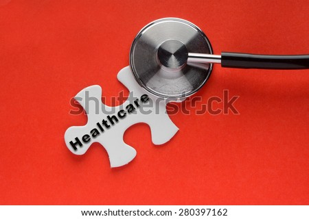Stethoscope on top of a white jigsaw puzzle with a written word Healthcare on a red background. - stock photo