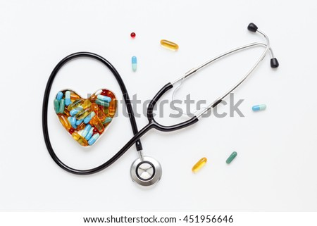 stethoscope on white background with pills in shape of heart - stock photo