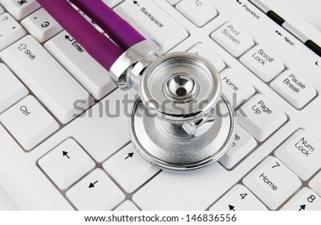 Stethoscope on white keyboard close up
